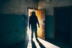 剪影犯罪或疯狂与刀子在手中在老可怕大厦,与冷的武器的连环杀手 免版税库存照片