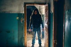 剪影犯罪或疯狂与刀子在手中在老可怕大厦,与冷的武器的连环杀手 免版税库存图片