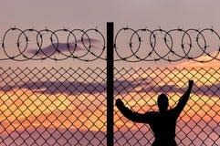 剪影男性难民和铁丝网篱芭 库存照片