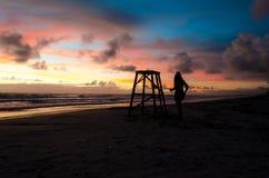 剪影的一名妇女在一个海滩的一个救生员塔旁边与太阳上升和绘与橙色颜色的阳光天空 免版税图库摄影