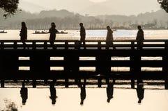 剪影的五个游人过桥梁在杭州` s西湖风景区 库存照片