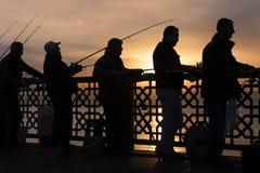 剪影的渔夫在日出,在加拉塔桥梁,在伊斯坦布尔,土耳其 免版税库存照片