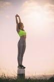 剪影行使在日落时间的健身妇女 库存照片