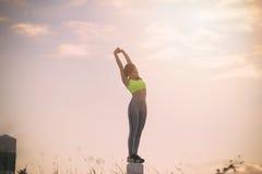 剪影行使在日落时间的健身妇女 免版税图库摄影