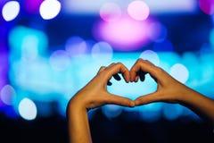 剪影观众心形的手和人群在生活音乐会,有启发性的轻的是音乐音乐会的力量 免版税图库摄影