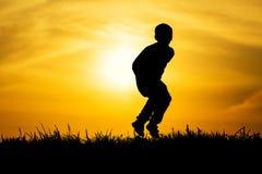 剪影跳跃了日落的男孩 库存照片