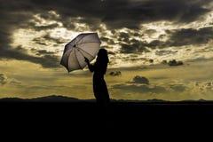 剪影,日落,拿着伞的夫人 免版税库存照片