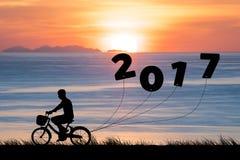剪影年轻人乘驾自行车在海和2017年,当庆祝新年好时 库存照片