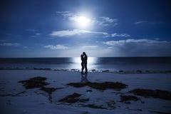剪影结合夜在海边 库存照片