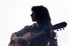 剪影 美丽的女孩在白色背景的一把声学吉他使用在阴霾 复制空间 一张方形的图片 免版税库存照片