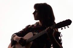 剪影 美丽的女孩在白色背景的一把声学吉他使用 复制空间 库存照片