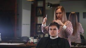 剪微笑的人客户的头发的女性美发师在美容院 影视素材