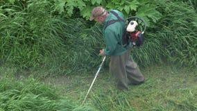 剪绿草的工作者在庭院里,使用手工汽油草坪整理者 影视素材