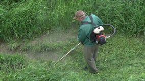 剪绿草的花匠在庭院里,使用手工汽油草坪整理者 股票视频