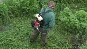 剪绿草的花匠在庭院里,使用手工汽油草坪整理者 影视素材