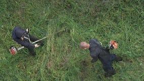 剪草的两位花匠在夏天庭院里,使用汽油草坪整理者 股票录像