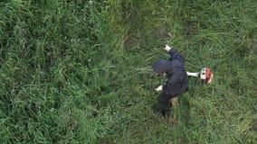 剪草的工作者在夏天庭院里,使用汽油草坪整理者 股票录像