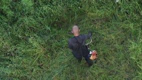 剪草的工作者在庭院里,使用手工汽油草坪整理者 股票录像