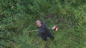 剪草的花匠在夏天庭院里,使用手工汽油草坪整理者 影视素材