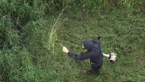 剪草的花匠在夏天庭院里,使用手工汽油草坪整理者 股票录像