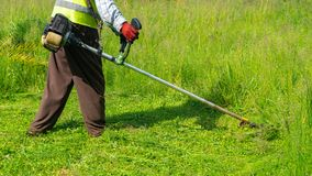 剪草的花匠由割草机,草坪关心 免版税库存照片