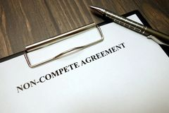 剪贴板与非竞争协议和笔在书桌上 免版税图库摄影