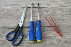 剪,螺丝刀和镊子在灰色木书桌上 库存图片