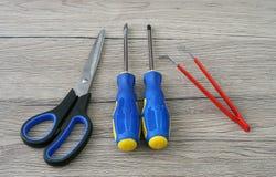 剪,螺丝刀和镊子在表上 免版税库存图片