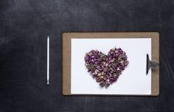 剪贴板与和花的心脏在黑背景的 Valen 免版税库存图片