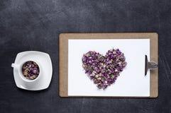 剪贴板与和花的心脏在黑背景的 Valen 免版税库存照片