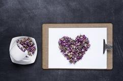 剪贴板与和花的心脏在黑背景的 Valen 图库摄影