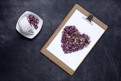 剪贴板与和花的心脏在黑背景的 Valen 免版税图库摄影