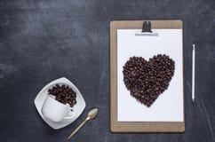 剪贴板与和花的心脏在黑背景的 Valen 库存图片