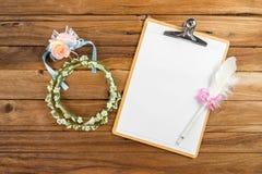 剪贴板附上与笔的计划纸在玫瑰色头饰带旁边 免版税库存照片