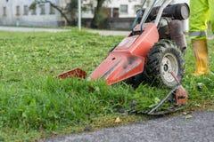 割与刈草机草的农夫 免版税库存图片