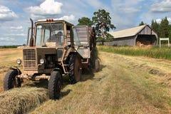 割晒牧草时间,有圆的打包机的俄国农用拖拉机收获h 免版税库存照片