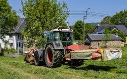 割晒牧草,拖拉机 图库摄影