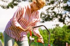 割有割草机的妇女草坪 免版税库存照片