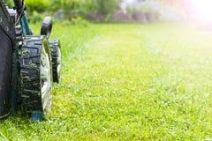 割的草坪,在绿草,刈草机草设备,割的花匠关心工作工具,看法,晴天的关闭的割草机 虚拟 免版税图库摄影