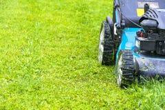 割的草坪,在绿草,刈草机草设备,割的花匠关心工作工具,看法,晴天的关闭的割草机 免版税库存照片