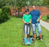 割草坪和一起整理边缘的父亲和儿子 免版税库存图片