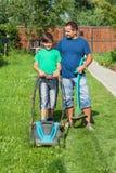 割草坪的父亲和儿子 图库摄影