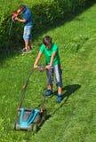 割草坪的男孩,当他的父亲整理树篱时 免版税库存图片