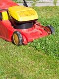 割草机割绿色草坪 免版税库存照片
