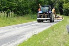割草的拖拉机在乡下公路一边 免版税库存图片