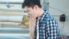 割破他的手指的年轻工人,运转在车间 库存照片