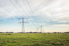力量定向塔行与高压线的在荷兰开拓地风景 免版税库存图片