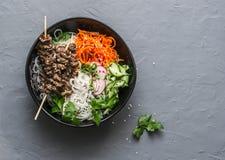 力量平衡的菩萨碗 亚洲样式牛肉串,米细面条,泡菜沙拉红萝卜,黄瓜,萝卜,草本 免版税库存照片