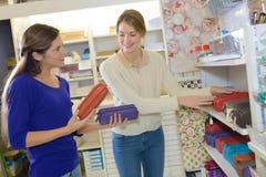 劝告女性的卖主关于学校用品的父母顾客 免版税库存图片