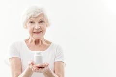劝告愉快的老妇人采取药片 免版税图库摄影